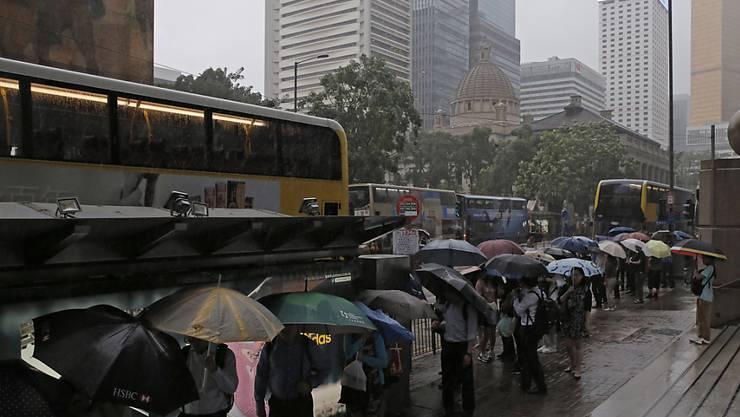 """Auch in Hongkong haben Passanten die Regenschirme aufgespannt, um sich vor den Tropfen zu schützen, die Taifun """"Merbok"""" der Region beschert."""