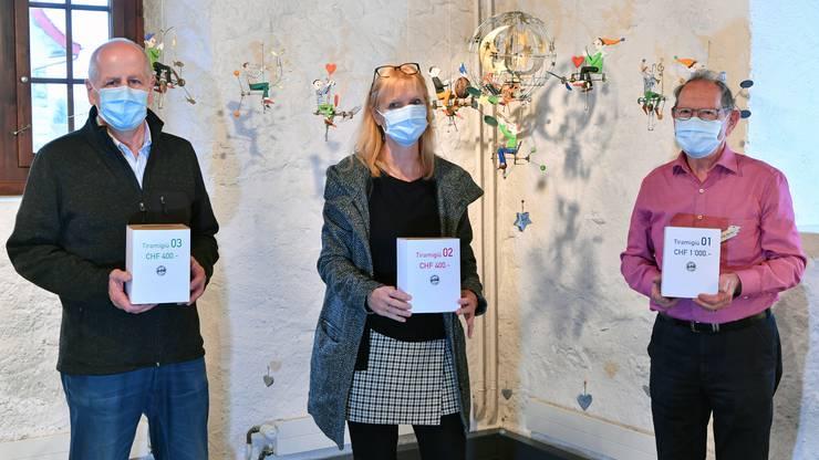 V.l.n.r.: Martin Planzer, Madeleine Kuhn und Christian Tännler mit drei der zehn Los-Boxen, aus denen nach der Ausstellung je ein Namensschild gezogen wird, das zum Kauf einer Gugelmann-Figur berechtigt.