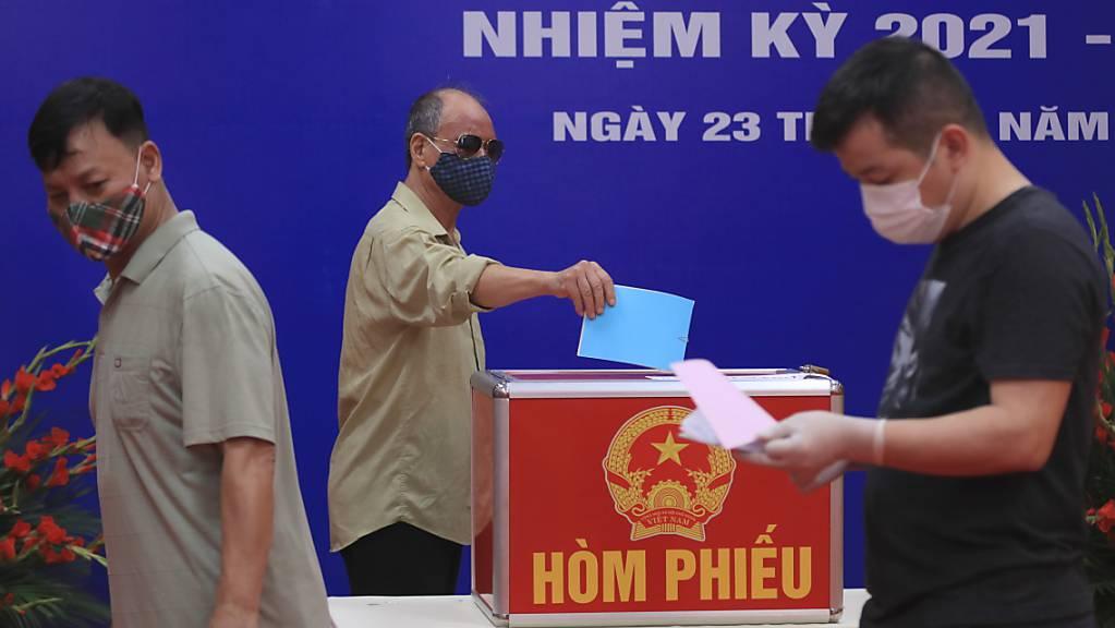 Menschen mit Mund-Nasen-Schutz stimmen bei der Wahl der Nationalversammlung in einem Wahllokal ab.