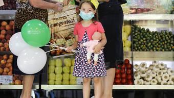 Ein Mädchen mit medizinischem Mundschutz hält Luftballons und eine Puppe in einem Lebensmittelmarkt in Bukarest. Rumänien verzeichnet einen Rekord an Neuinfektionen mit dem Coronavirus. Foto: Vadim Ghirda/AP/dpa