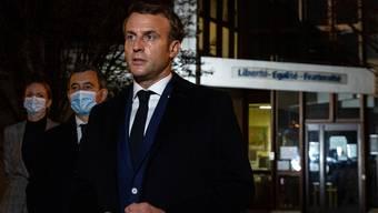 Frankreichs Präsident Emmanuel Macron (r) mit Innenminister Gerald Darmanin (2. v.l.), vor der Schule in Conflans Saint-Honorine nahe Paris: Hier unterrichtete Samuel Paty, bevor er Ende letzter Woche Opfer eines grausamen Mordanschlags wurde.