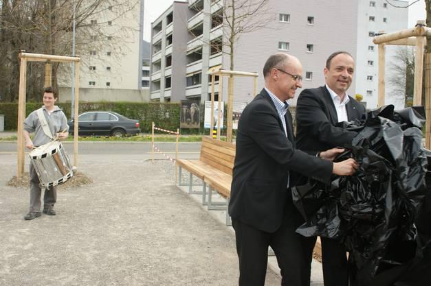 Unter Trommelwirbeln wird die neue Parkbank aus Nussbaumholz in Anwesenheit von Behördenvertretern enthüllt.
