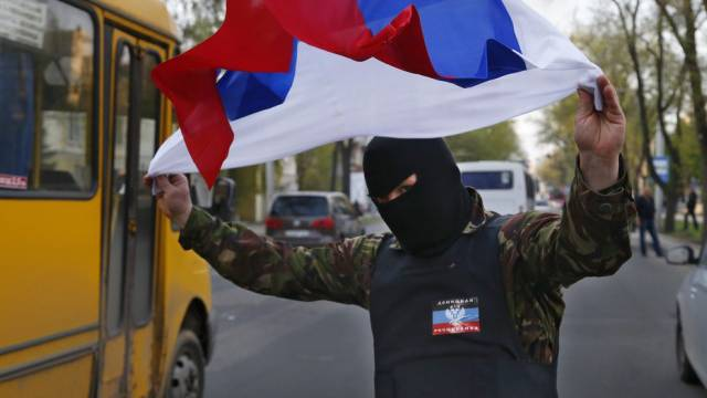 Ein prorussischer Aktivist schwenkt eine russische Fahne in Donezk