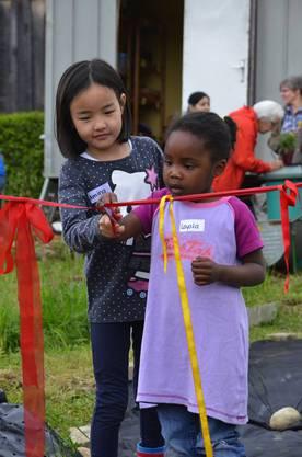 Amina und Layola, die Kinder zweier Flüchtlingsfrauen, eröffnen die neuen Parzellen im interkulturellen Garten in Baden-Rütihof