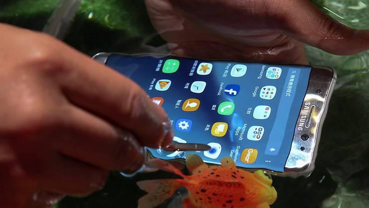 Samsung-Handys werden in der Werbung auf dem Boden eines Schwimmbeckens oder im Meer benutzt. Das hat dem Telekomkonzern nun eine Klage der australischen Wettbewerbsbehörde eingebrockt. (Archiv)