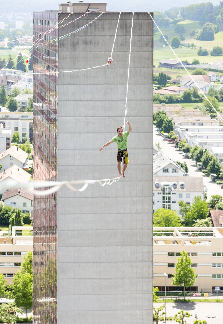 «70 Meter über dem Boden: Auf dem Dach des Shoppi-Tivoli-Hochhauses in Spreitenbach muss ich mich leicht über die Brüstung lehnen, um ein gutes Bild zu schiessen. Etwas mulmig ist mir schon. Denn vor mir balancieren wagemutige Sportler stundenlang auf 2,5 cm breiten Stoffbändern, sogenannten Highlines, zwischen den Hochhäusern hin und her. Die Aktion soll Spendengelder sammeln und wird den Weltrekord brechen. Unter den Athleten: der freie Fall. Über ihnen: nur der Himmel.»
