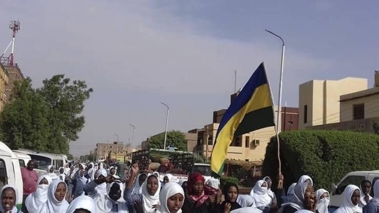 """In ihre Schuluniformen gekleidet und sudanesische Flaggen schwenkend skandierten am Dienstag Schülerinnen und Schüler Parolen wie """"Einen Schüler töten heisst ein Land zu töten"""". Bei Protesten gegen die Militärführung des Landes waren am Montag fünf Schüler getötet worden."""