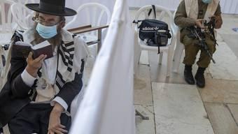 Ein ultra-orthodoxer jüdischer Mann betet in Jerusalem neben einem israelischen Soldaten. Foto: Ariel Schalit/AP/dpa