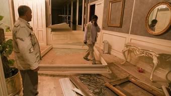 Wächter begutachten die Schäden im Gebäude Gaddafis