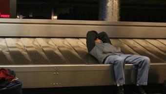 Ein Mann schläft auf einem Gepäckband (Archiv)