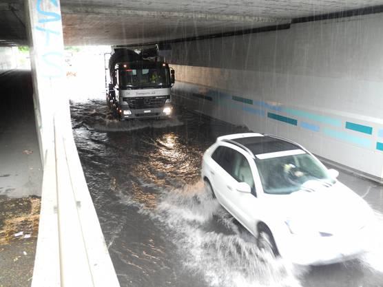 Autos kämpfen sich durch die Wassermassen.
