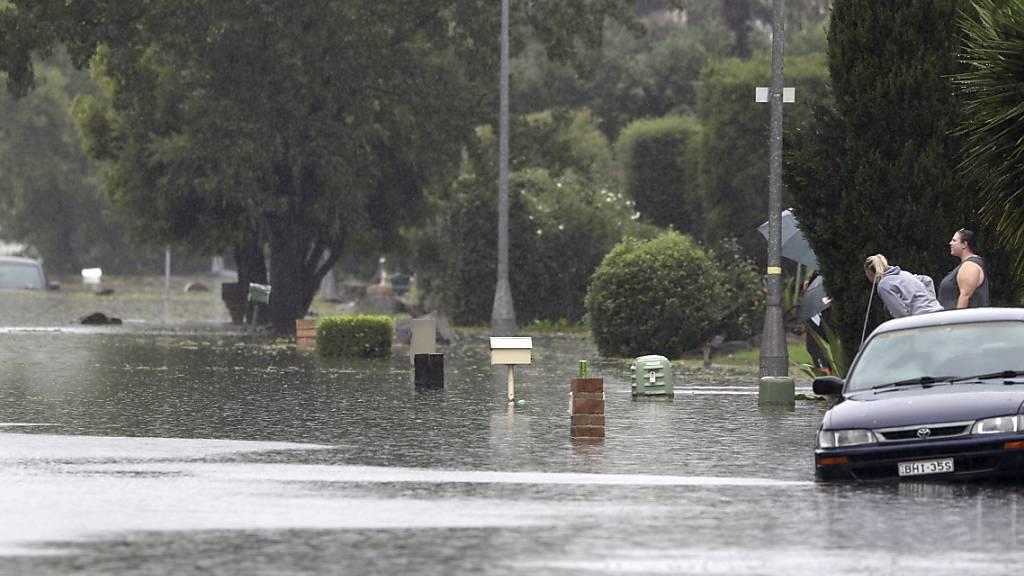 Zwei Frauen stehen neben einer überfluteten Straße. Tagelanger Starkregen hat im Südosten Australiens zu einem katastrophalen Hochwasser und der Evakuierung ganzer Ortschaften geführt. Foto: Rick Rycroft/AP/dpa