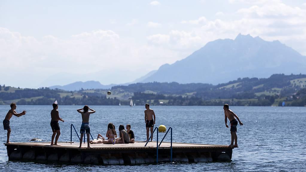 Menschen geniessen das schöne Wetter auf einem Floss im Seebad Seeliken in Zug. (Archivbild)
