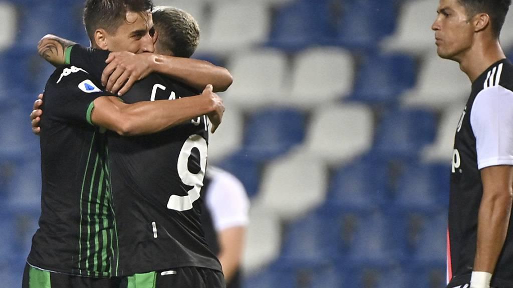 Sassuolos Torschützen Filip Djuricic (links) und Francesco Caputo feiern ihren Punktgewinn gegen Cristiano Ronaldos Juventus