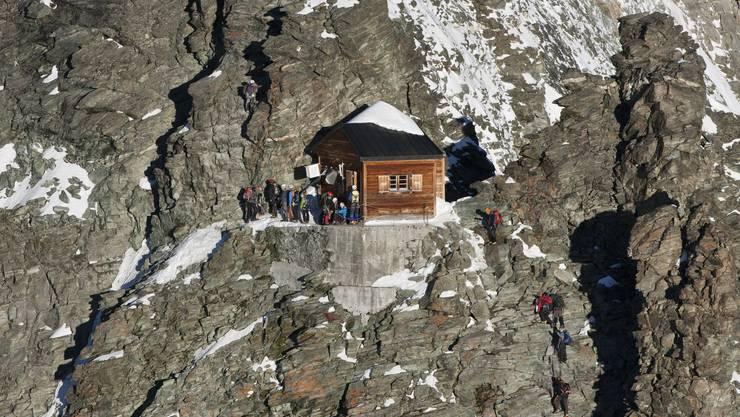 Der Name «Solvay» dürfte vielen Bergsteigern aus aller Welt bekannt sein: So mancher von ihnen hat schon in der Solvayhütte am Matterhorn Schutz gesucht. Was sie dabei wohl nicht wussten: Gestiftet wurde die 1915 errichtete Hütte vom belgischen Firmengründer Ernest Solvay. Dieser kam erst mit 57 Jahren zum Bergsport – dann aber so richtig: Mit 81 Jahren bestieg er noch Alpengipfel, zwei Tage vor seinem Tod mit 84 Jahren wanderte er 17 Kilometer.Die Solvayhütte ist die höchstgelegene SAC-Hütte der Schweizer Alpen. Sie liegt auf 4003 m ü. M. am Hörnligrat, der meistgenutzten Besteigungsroute des Matterhorns. Sieben bis acht Stunden dauert der Aufstieg von der Hörnlihütte aus, die rund 700 Meter unterhalb der Solvayhütte am Fusse des Matterhorns liegt.Die Solvayhütte selbst ist lediglich als Notunterkunft gedacht. Sie ist nur über einen als «sehr schwierig» gekennzeichneten Weg zu erreichen. Dieser führt von Zermatt aus hinauf zum Schwarzsee, weiter zur Hörnlihütte und schliesslich über den Hörnligrat. Zwischen der unteren und der oberen Mosleyplatte stösst man dann auf die kleine Holzhütte. Ein Grossteil des Anstieges führt über Schutt und Geröll. Oberhalb der Solvayhütte sollten sich Bergsteiger nur noch angeseilt und gesichert fortbewegen. Weil die verhältnismässig einfache Hörnligrat-Route immer wieder Amateure ohne Bergführer anzieht, wird die Hütte relativ häufig genutzt. (NRO)