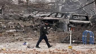 Ein Polizeibeamter überquert das Trümmerfeld, das die Explosion hinterlassen hat.