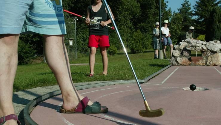 Eine Familie lässt sich nicht nehmen, trotz der Hitze Minigolf zu spielen. Foto vom 17. Juli 2005 in der Minigolfanlage von Windisch. Zeit: 18.11 Uhr.