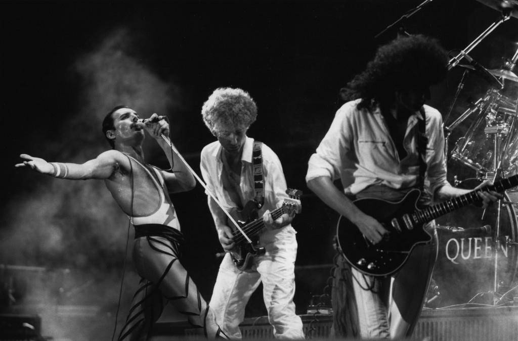 Freddie Mercury mit John Deacon und Brian May am 1. Januar 1984 (© Getty Images)