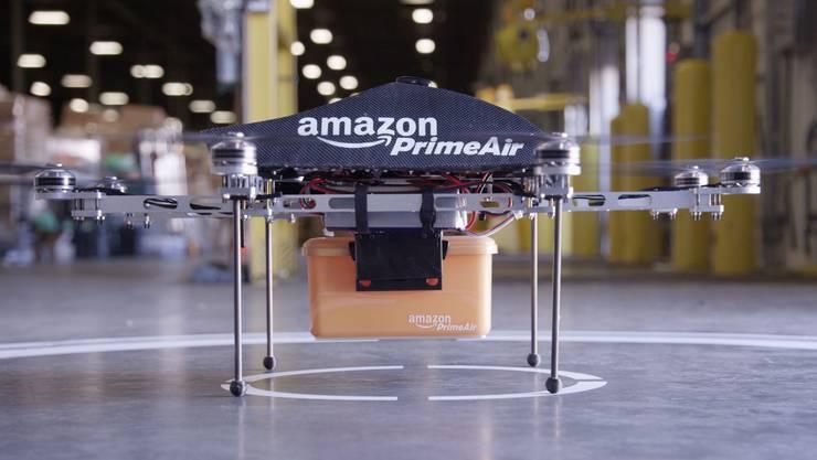 Eine Mini-Drohne des Online-Händlers Amazon inklusive befestigter Paketkiste. Amazon will in Zukunft Bestellungen mit automatischen Mini-Drohnen zustellen. Die bestellte Ware soll damit in30 Minuten zum Käufer gebracht werden.