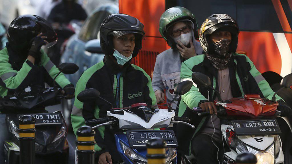 Eine Alternative im ewigen Stau: Die Motorrad-Taxis schlängeln sich gekonnt durch die Blechlawine in Jakarta.