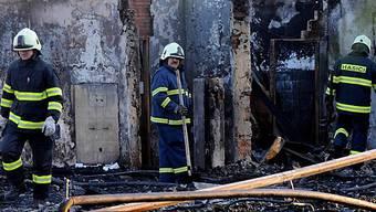 Feuerwehrleute inspizieren das abgebrannte Gebäude in Prag