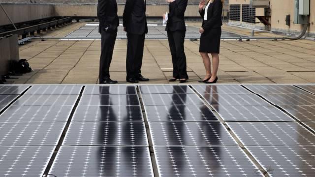 Obama (2. v. l.) neben Solarpanels auf einem Behördengebäude