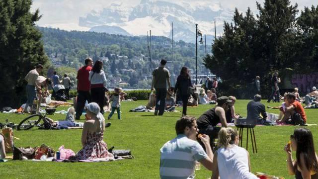 Menschen geniessen die warmen Temperaturen in einem Zürcher Park