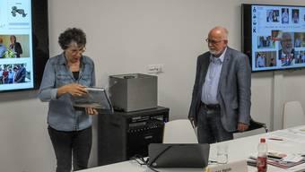 Bruno Breitschmid wird als Präsident verabschiedet, Rosmarie Groux übergibt ihm Geschenke.