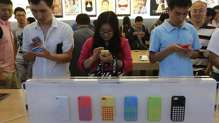 Kunden begutachten iPhone-Modelle im Apple-Store in Peking. Nach Aussagen von Apple-Chef Tim Cook kaufen die Chinesen trotz Sorgen um eine Abschwächung des Wirtschaftswachstums weiterhin fleissig Apple-Produkte. (Archiv)