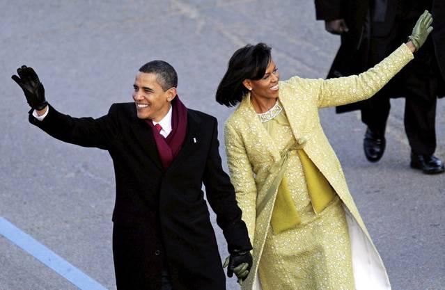 Barack Obama winkt auf die eine Seite, seine Frau Michelle auf die andere: Der Start zu seiner Präsidentschaft nachdem er bei der Amtseinführung den Eid geschworen hat. (20. Januar 2009)