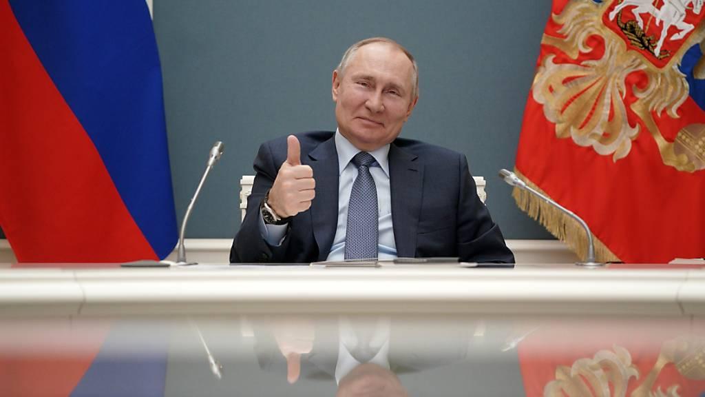 HANDOUT - Wladimir Putin, Präsident von Russland, zeigt während einer Videokonferenz mit dem türkischen Präsidenten Erdogan seinen Daumen nach oben. Zum Baubeginn eines weiteren Reaktors für das erste türkische Atomkraftwerk Akkuyu haben Präsident Erdogan und Russlands Staatschef Putin die Zusammenarbeit beider Länder gelobt. Foto: Alexei Druzhinin/Pool Sputnik Kremlin/AP/dpa - ACHTUNG: Nur zur redaktionellen Verwendung und nur mit vollständiger Nennung des vorstehenden Credits