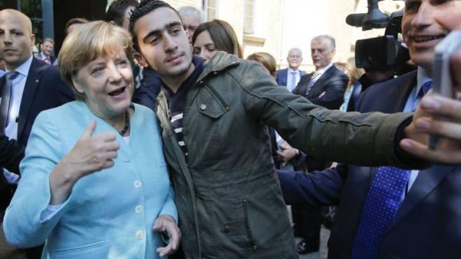 Angela Merkel posiert mit einem Flüchtling: «Weiss sie, was sie tut?», fragen die Medien. Foto: Reuters