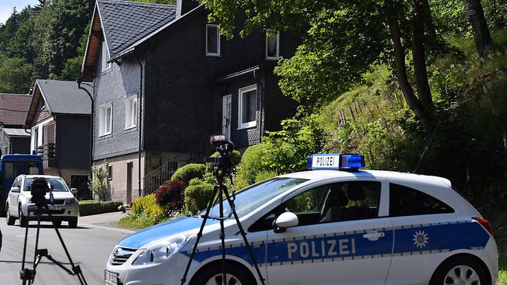 Ein Polizeiauto und Kameras stehen vor dem Haus (vorne rechts) im thüringischen Altenfeld, in dem sich das Familiendrama ereignete.