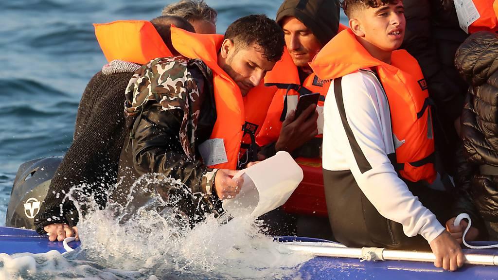 ARCHIV - Eine Gruppe von mutmaßlichen Migranten überquert den Ärmelkanal in einem kleinen Boot in Richtung Dover. Foto: Gareth Fuller/PA Media/dpa