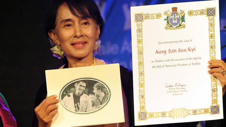 """Aung San Suu Kyi mit der Urkunde der Menschenrechtsorganisation Amnesty International, die ihr 2009 den Ehrentitel """"Botschafterin des Gewissens"""" verliehen hatte. Nun hat Amnesty Suu Kyi den Titel entzogen.  (Foto: KIM HAUGHTON/EPA)"""