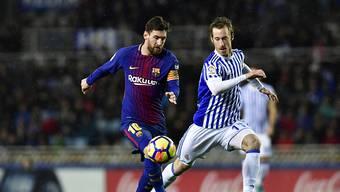 Barcelonas Lionel Messi (links) überläuft David Zuturuza von San Sebastian