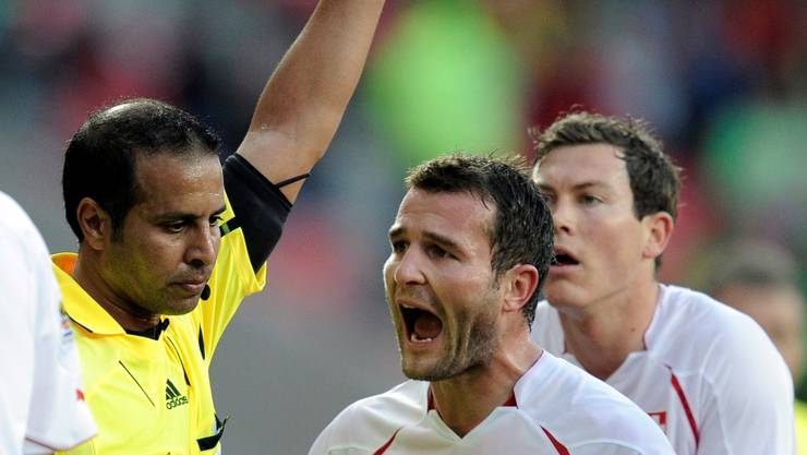 Switzerland's Alex Frei, right, argues with referee Khalil Al Ghamdi of Saudi Arabia after Switzerland's Valon Behrami, not seen, was shown a red card during the World Cup group H soccer match between Chile and Switzerland at Nelson Mandela Bay Stadium in Port Elizabeth, South Africa, Monday, June 21, 2010.  (AP Photo/Martin Meissner)
