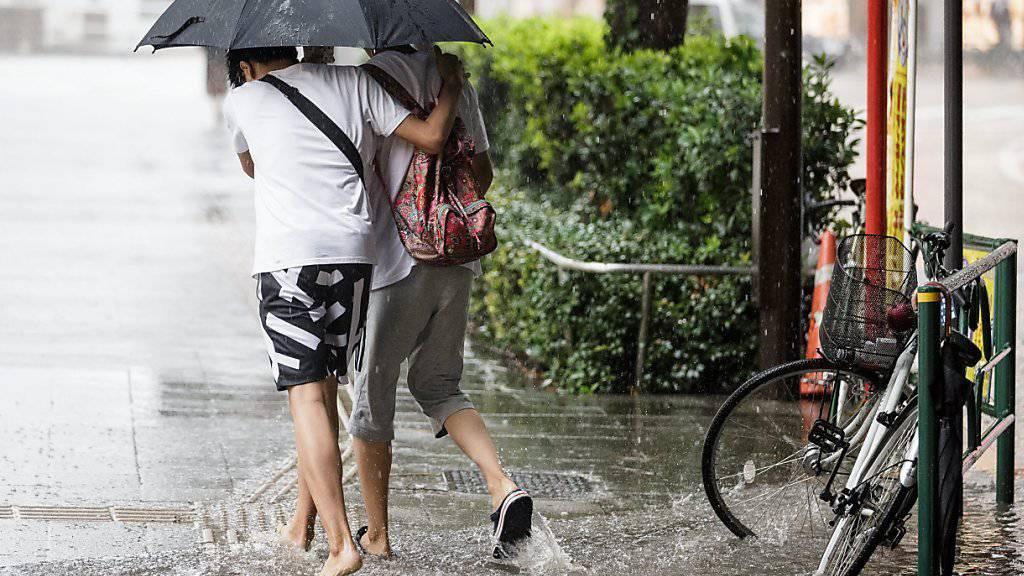 Zwei Fussgänger waten in Tokio durch eine teilweise überschwemmte Strasse.