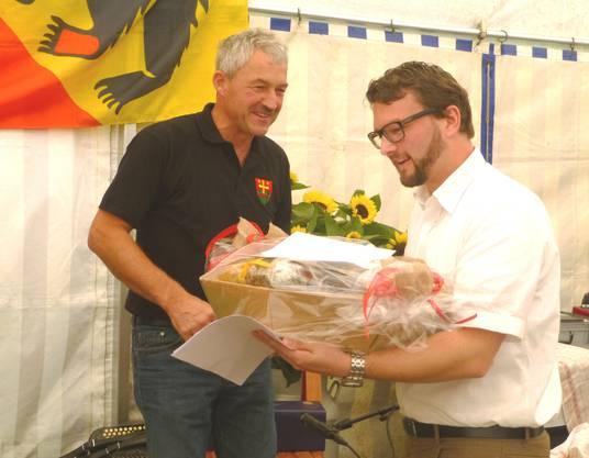 Burgerpräsident Hanspeter Hohl überreicht Regierungsstatthalter Marc Häusler eine Auswahl an Attiswiler Produkten.
