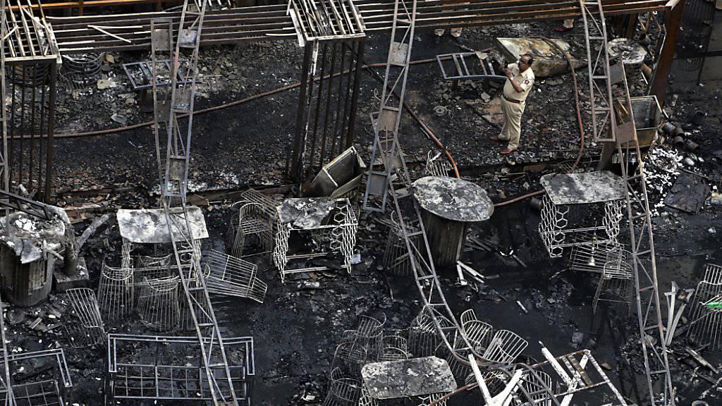 Ermittler in den Überresten des niedergebrannten Restaurants in Mumbai