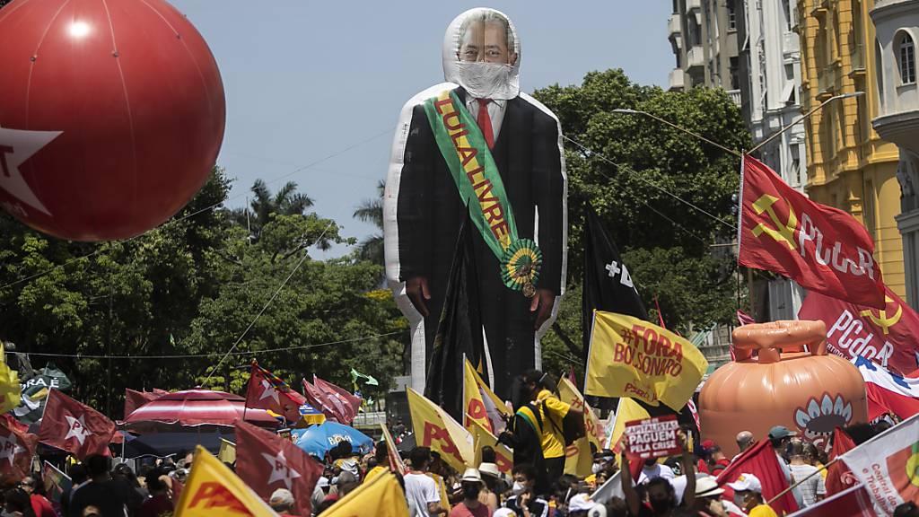 Eine riesige Figur von Ex-Präsident Luiz Inacio Lula da Silva überragt die Demonstranten während einer Demonstration gegen den brasilanischen Präsidenten Bolsonaro. Foto: Bruna Prado/AP/dpa