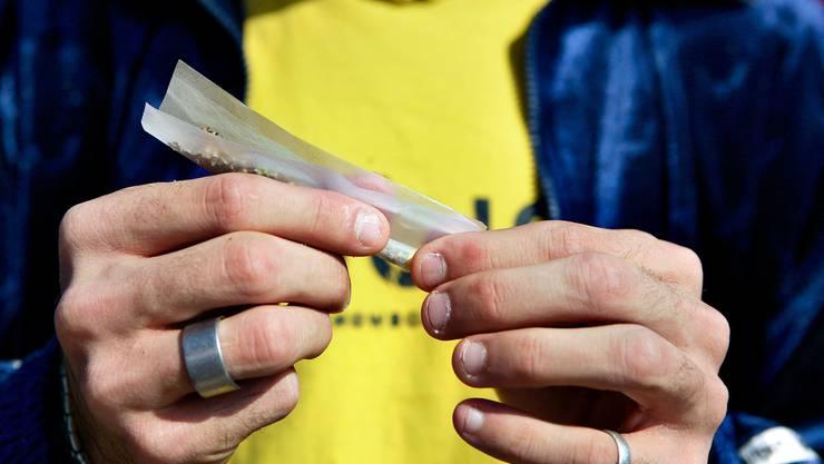 Trotz Verbot: Ein Jugendlicher dreht einen Joint.