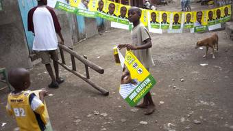Anwohner hängen Plakate für die Wahlen am Sonntag auf