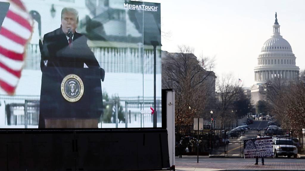 Ein Foto des ehemaligen US-Präsidenten Trump ist auf einem Monitor zu sehen, der auf einem Anhänger in der Nähe des US-Kapitols geparkt ist. Foto: Jose Luis Magana/AP/dpa