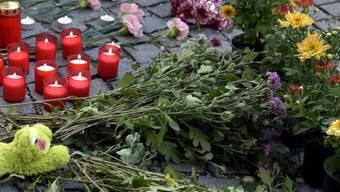 Blumen und Kerzen vor der Polizeidirektion Eisenstadt im österreichischen Burgenland zum Gedenken an die in einem Lastwagen gefundenen toten Flüchtlinge.