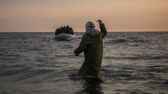 Ein Helfer winkt Neuankömmlingen auf einem Flüchtlingsboot an der griechischen Küste zu.