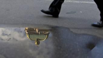 Die Kuppel des Bundeshauses spiegelt sich in einer Pfütze (Symbolbild)