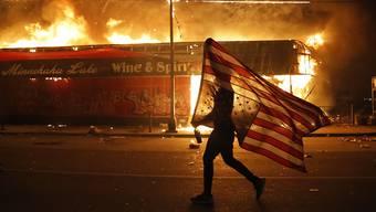 Ein Demonstrant vor einem brennenden Gebäude mit einer eine US-Flagge. Foto: Julio Cortez/AP/dpa