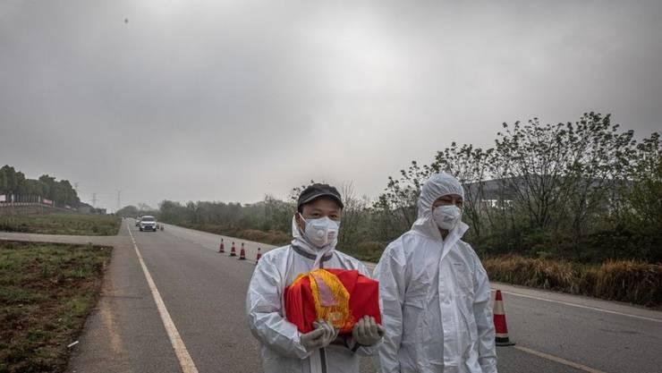Ein Paar in Wuhan trägt die Asche eines Verwandten nach Hause. Die drastischen Sperrmassnahmen in Wuhan, welches als Epizentrum der Covid-19-Epidemie gilt, hat genützt, wie eine Studie beweist.