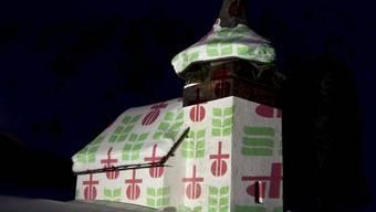 Lichtprojektion der Embleme von Fastenopfer und Brot für alle auf einem Bergkirchlein (Archiv)